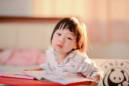 intelligently: Cute Asian girl reading a book with nature rim light. Stock Photo