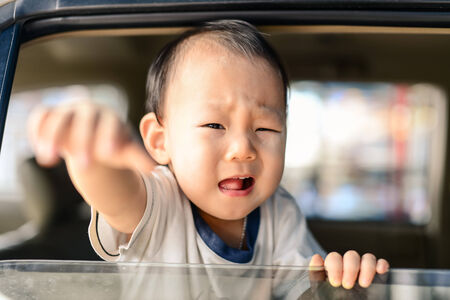 Crying Asian baby in car, safety concept. Banco de Imagens