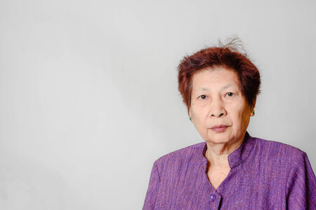 Portrait of Asian elderly woman, isolated over grey background.
