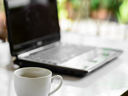 Coffee cup and laptop for business, Selective focus on coffee. photo