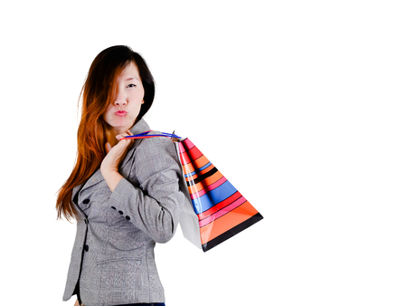 Thoughtful elegant Asian woman with colorful shopping bags. photo