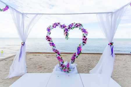 set up: Flower decorated in heart shape in wedding ceremony which set up on the beach.