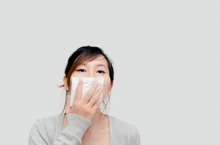 Sick woman blowing her nose isolated. photo