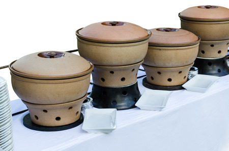 chafing dish: Thai clay pottery chafing dish heaters at the banquet table with clipping path Stock Photo