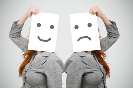 Business-Frau mit einem Lächeln und trauriges Gesicht auf weißem Vorstand Lizenzfreie Bilder