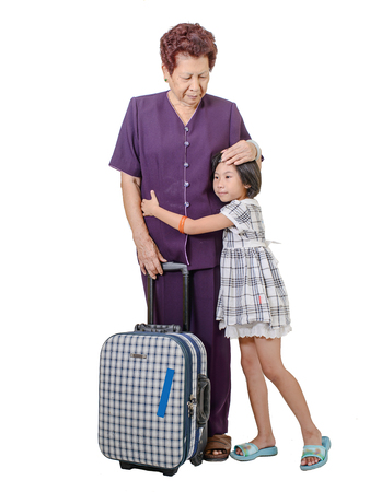 Senior woman hugging crying girl with suitcase, isolated on white.