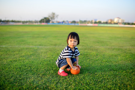 Asian girl playing ball in green field. photo