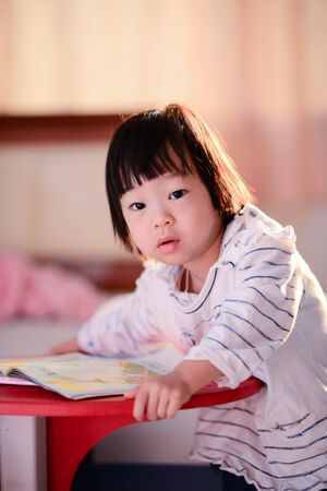 Cute Asian girl reading a book with nature rim light. photo