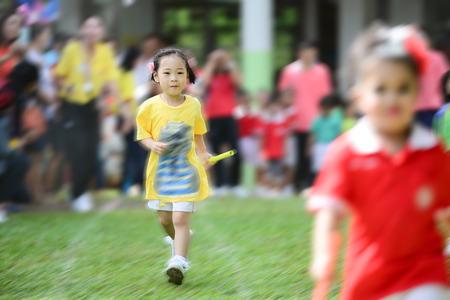 Cute Asian girl running in sport day.