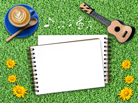 Notepad on an artificial Grass with guitar. photo