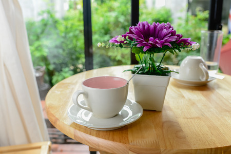 pot light: Coffee mug and flower pot on wooden table.