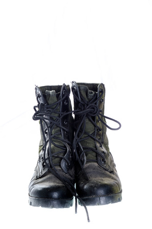 combat boots: Old and dusty combat boots isolated on white.