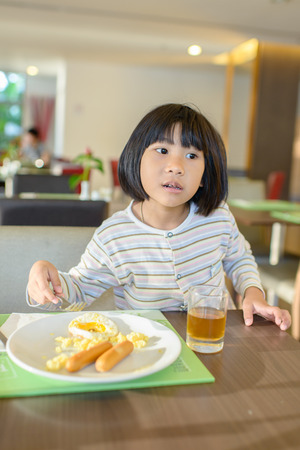 provocative food: Asian girl eating breakfast with pajamas.