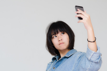 Cute Asian teenager using cellphone for selfie. photo