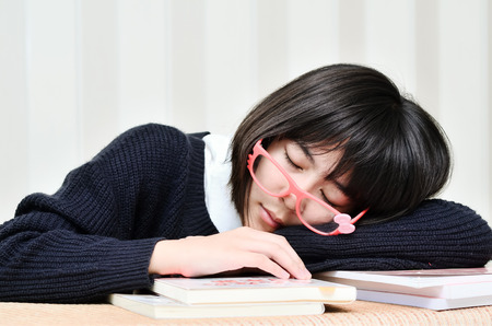 very tiredexhausted, pretty, female student with books working in a high school. photo
