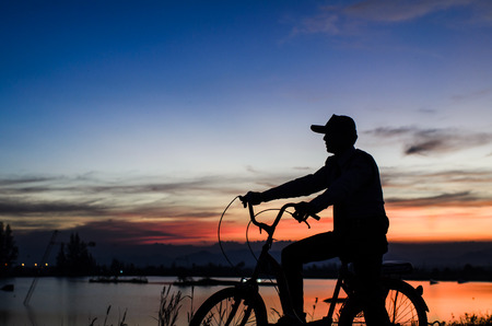 cycler: Cycler silhouette in sunrise against sun set cloudy sky Stock Photo