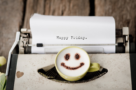 Happy Friday on typewriter with happy face coffee cup, sepia tone. Stock Photo