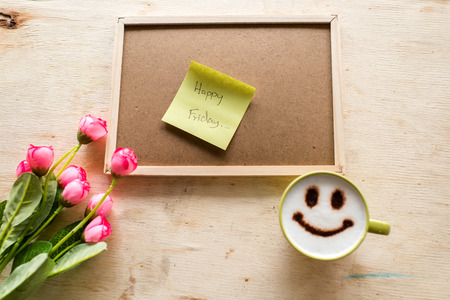 Happy Friday on paper note with corkboard coffee up and pen on wooden background