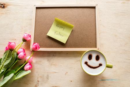 Glücklicher Freitag auf Papier Hinweis mit corkboard Kaffee und Stift auf Holzuntergrund