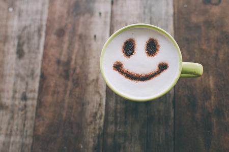 s úsměvem: Šťastný obličej na šálek kávy na dřevěném pozadí s vintage barevný efekt. Zátiší.