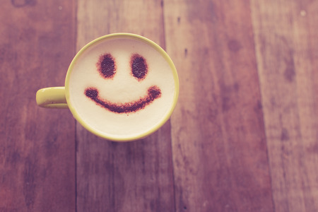 coffee froth: Happy face on coffee cup on wooden background with vintage colour effect. Still life.