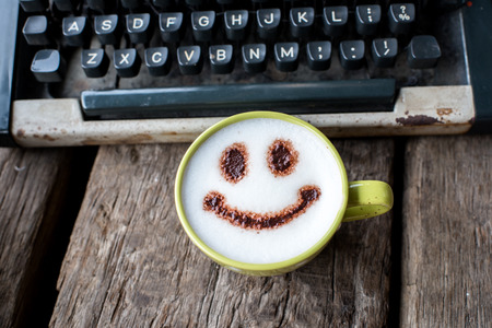 Happy coffee cup and Vintage typewriter on wooden background. photo
