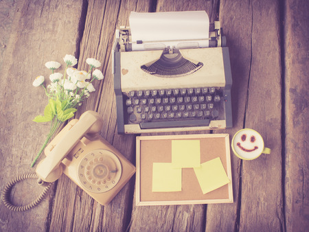 vintage typewriter and telephone and happy coffee mug on the wood desk in vintage color tone photo