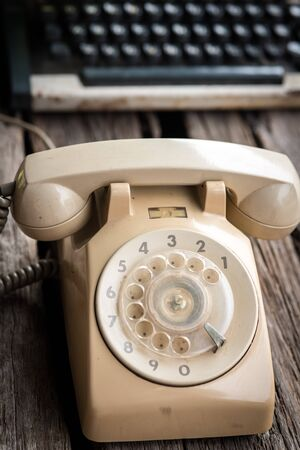 Retro rotary telephone  and typing machine on wooden background. photo