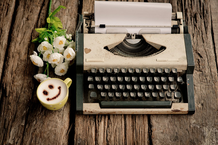 vintage typewriter and telephone , notebook on the wood desk in vintage tone.