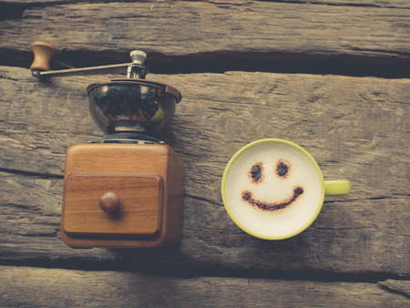 nostalgic: Nostalgic coffee grinder happy coffee cup and handmade note book on wooden background. Stock Photo