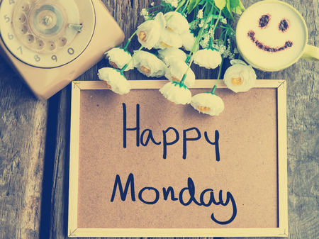 monday: Happy Monday message on corkboard, telephone, happy coffee cup with vintage tone.