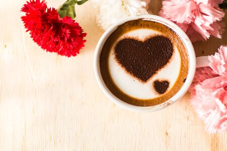 Love message on coffee cup on wooden background with vintage colour effect. Still life. photo