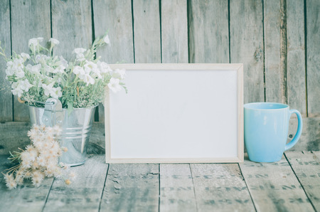 Vintage style White flowers stainless pot and blue pastel tea cup on wooden background, still life photo