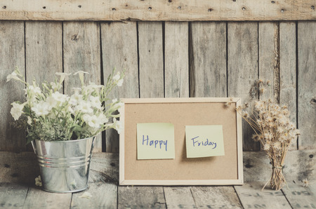 Vintage style effect Happy Friday message on corkboard with flowers  by wooden background Stock Photo