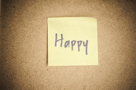 sticky hands: Happy note message on sticky paper by corkboard. Stock Photo
