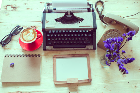 flat view retro office, telephone, typewriter and coffee cup placed near  red coffee cup on wooden table photo