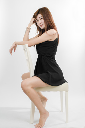 portrait of Asian woman sitting on chair isolated on white photo