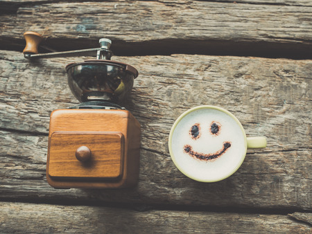 Nostalgic coffee grinder happy coffee cup and handmade note book on wooden background. photo