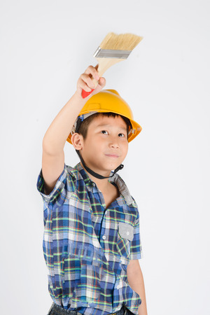 Asian boy in a protective helmet with brush in his hand photo