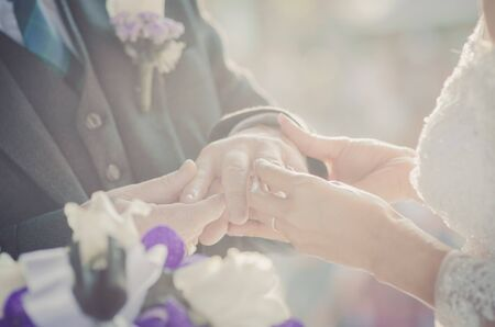 Bride Put the Wedding Ring on groom hand photo
