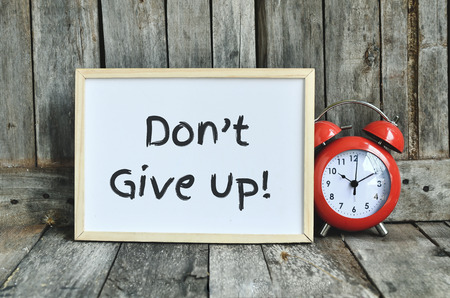 not give: Dont give up  message note on white board with red retro clock on wooden background.