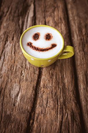 Latte Art, grünen Kaffeetasse auf hölzernen Hintergrund mit Vintage-Farbeffekt.