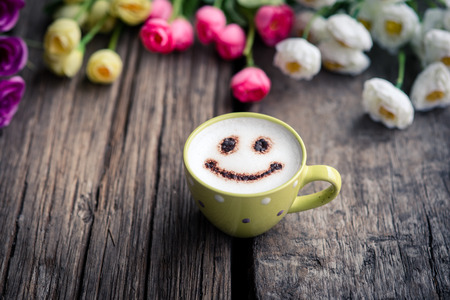 Wood background with spring flowers, colour tone and coffee cup.
