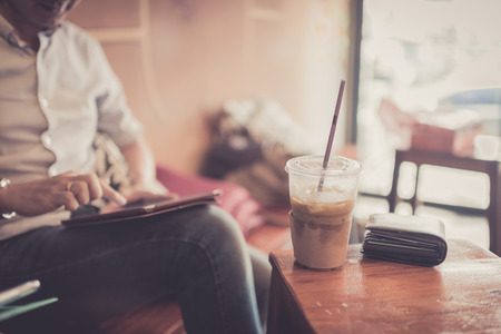 cafe: Ice coffee in plastic glass with wallet in cafe with businessman  using tablet background.