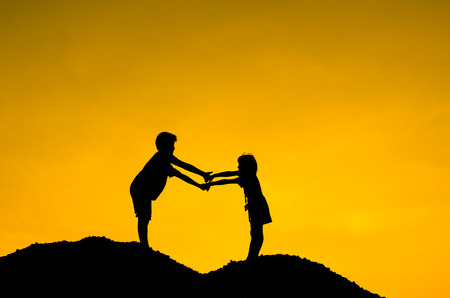 Two children during sun set, holding hands together. photo