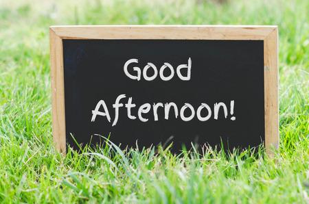 緑の芝生に黒板に良い午後メッセージ。 写真素材