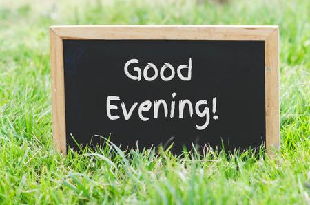 bonsoir: Bon message en soir�e sur le tableau noir sur l'herbe verte.