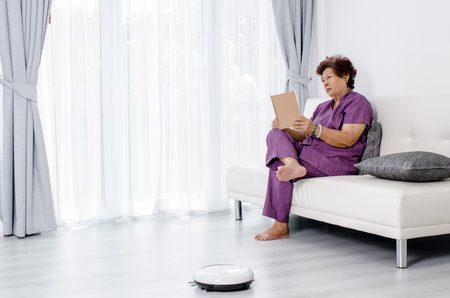happy asian people: Senior woman reading a book while robot vacuum cleaning floor at home. Modern lifestyle concept. Stock Photo