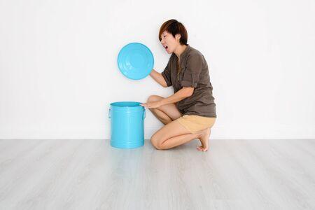 poubelle bleue: Femme asiatique intelligente ouverture bac bleu � la maison. Banque d'images
