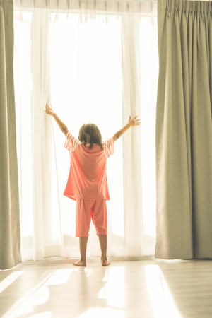 Girl standing at window holding curtains open to look out of large light window at home, instragram look. Stock Photo